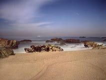 空的多岩石的海滩在晚上 免版税库存图片