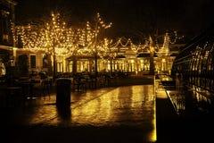 空的夜餐馆、没有一个的全部桌和椅子,在树的不可思议的彩色小灯喜欢圣诞节庆祝 免版税库存图片