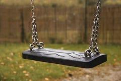 空的孩子在链子在一个秋季庭院里,概念摇摆  库存照片