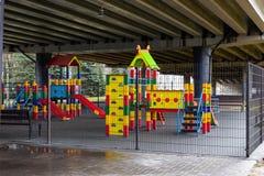 空的孩子的操场在有金属篱芭的路桥梁下 免版税库存照片