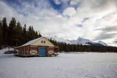 空的小屋和小船在冬天高山的结冰的湖, maligne湖,碧玉国家公园,加拿大靠码头 库存图片