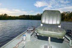 空的小船渔椅子和日落河场面 库存图片