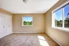 空的房子 有地毯地板的室在软的米黄颜色 图库摄影