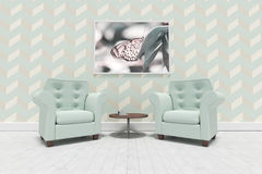 空的扶手椅子和桌的综合图象反对空白的画框 图库摄影