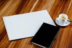 空的报纸、笔记本和浓咖啡在一张木桌上 免版税库存照片