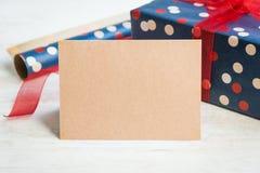 空的招呼的卡拉服特卡片 被包裹的礼物和包装用材料在白色木背景 免版税库存图片