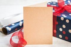 空的招呼的卡拉服特卡片 被包裹的礼物和包装用材料在白色木背景 库存照片
