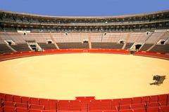 空的斗牛场在有红色圆环和蓝天的对比颜色的西班牙 免版税库存照片