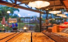 空的木桌和咖啡店弄脏与bokeh imag的背景 库存照片
