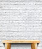 空的木桌和白色砖墙在背景中,嘲笑临时雇员 免版税库存图片