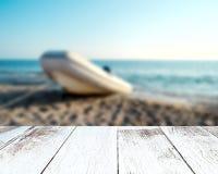 空的木桌板条 在沿海的被弄脏的小船 库存图片
