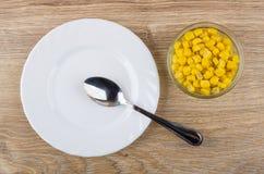 空的板材、匙子和碗用甜玉米在桌上 免版税图库摄影