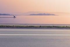 空的柏油路和湖侧视图  库存图片