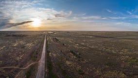 空的柏油路进入在日落的距离 免版税库存照片