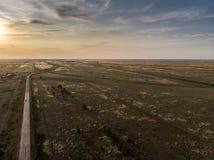 空的柏油路进入在日落的距离 免版税库存图片