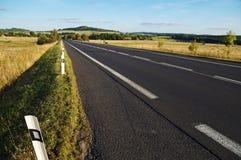 空的柏油路通过往天际的领域在一个农村风景 免版税库存照片