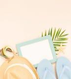 空的框架和暑假项目在奶油背景 草帽、蓝色触发器和木镯子 选择聚焦 安置fo 免版税库存图片