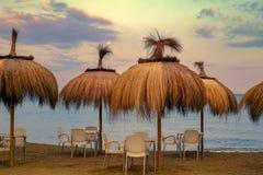 空的桌和椅子与秸杆伞在海滩 图库摄影