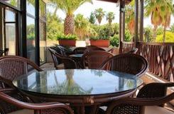 空的桌和椅子在一个咖啡馆在一个闭合的大阳台在旅馆里 免版税库存图片