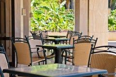 空的桌和椅子在一个咖啡馆在一个闭合的大阳台 库存照片