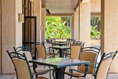 空的桌和椅子在一个咖啡馆在一个闭合的大阳台 免版税库存照片