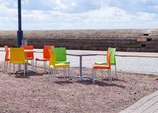 空的桌和美丽的五颜六色的塑料椅子在街道 库存图片