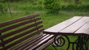空的桌和长凳在围场被透湿,湿下面雨,在操场, 大雨,雷暴, a 股票录像