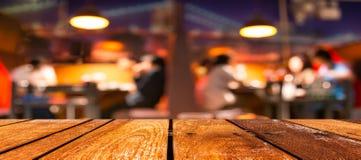 空的棕色木桌和咖啡店弄脏与bokeh图象的背景 免版税库存照片