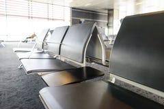空的椅子在离开大厅里在机场,与一个旅客的blured剪影的火车站在窗口附近的 旅行 免版税图库摄影