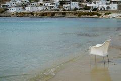空的椅子场面在白色藤条坐沙子海滩与软的波浪在清楚的海水和白色大厦的在防波堤 图库摄影