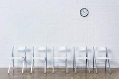 空的椅子行由白色砖墙的 库存图片