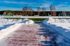 空的橄榄球(Soccer)领域在冬天在雪-晴朗的冬日部分包括 免版税库存照片