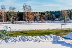 空的橄榄球(Soccer)领域在冬天在雪-晴朗的冬日部分包括 图库摄影