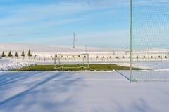空的橄榄球(Soccer)领域在冬天在雪-晴朗的冬日部分包括 库存图片