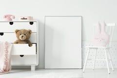 空的海报大模型在内阁有玩具熊的和白色之间的 图库摄影