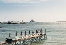 空的海滩休息室行在胡安les别针,法国有超级游艇的在背景中 库存照片