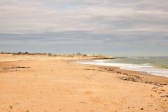 空的海滩在多云天空下 库存图片