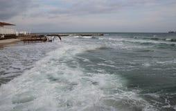 空的海滩多云秋天天气的黑海 与风雨如磐的海波浪的风景打破关于空的狂放的海滩 库存图片