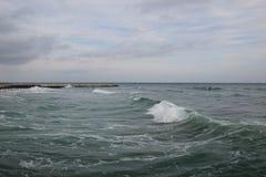 空的海滩多云秋天天气的黑海 与风雨如磐的海波浪的风景打破关于空的狂放的海滩 免版税库存图片