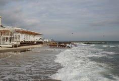 空的海滩多云秋天天气的黑海 与风雨如磐的海波浪的风景打破关于空的狂放的海滩 图库摄影