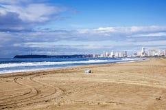 空的海滩和垃圾桶反对城市地平线 库存图片