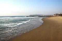 空的海滩和码头反对沿海地平线 免版税库存照片