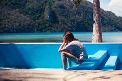 空的游泳池的哀伤的妇女 库存照片