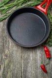 空的煎锅和草本在木背景 库存图片