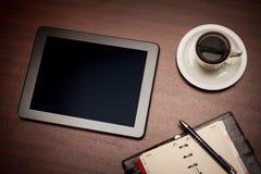 空的片剂和一杯咖啡在办公室 免版税库存图片