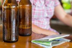 空的瓶与冒汗的下落的啤酒在地图旁边的一张木桌上 库存图片
