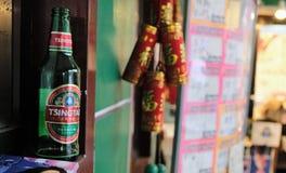 空的瓶与模糊的烟花串的青岛啤酒在背景中 免版税库存图片