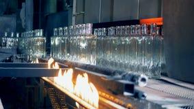 空的瓶在一台传动机的火附近上升巴氏灭菌作用的,关闭  影视素材