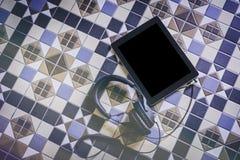 空的电子片剂屏幕大模型连接用在地中海砖地上的headphnes 空的大模型背景 免版税库存图片