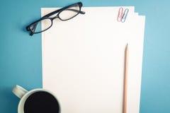 空的白皮书顶视图在蓝色背景的 库存图片